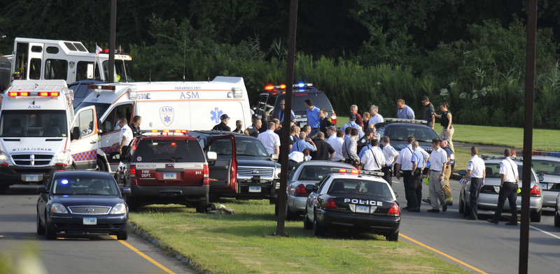 People are evacuated Tuesday from Hartford Distributors in Manchester, Conn., after a worker opened fire at the warehouse. As police arrived, some people were already hiding in the woods or under cars in the parking lot, the police chief said.