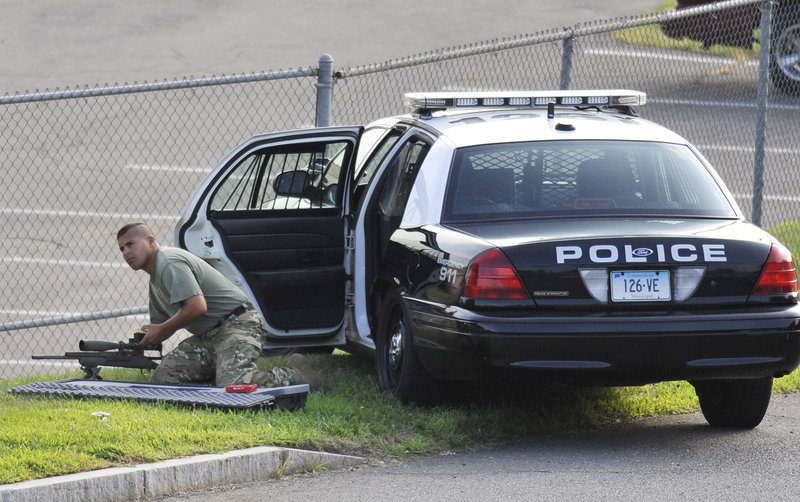 A police officer sets up his weapon outside Hartford Distributors. Gunman Omar Thornton was alive when police arrived at the scene but killed himself before officers got to him.