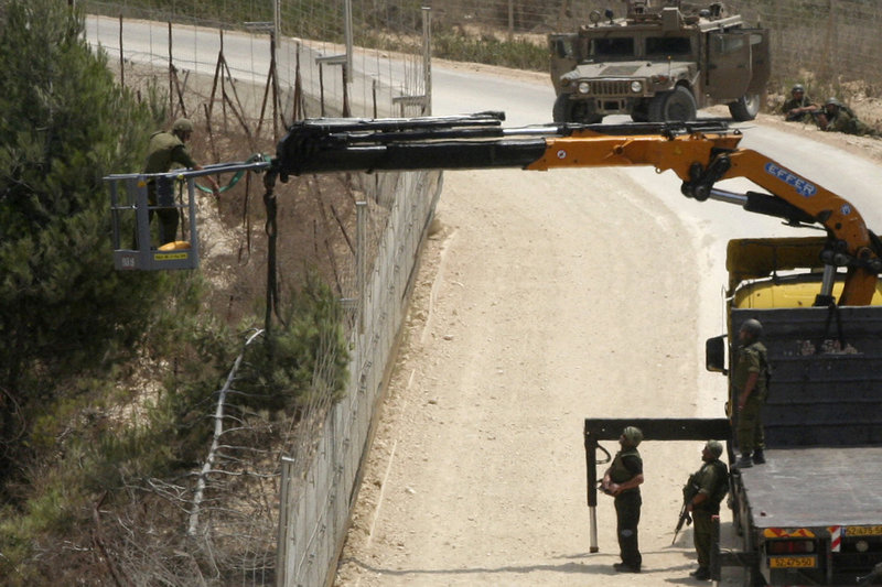 Israeli soldiers use a crane as they cut a tree Tuesday near the southern border village of Adeisseh, Lebanon. Israel and Lebanon each claimed the tree was in its territory. The sides exchanged fire, but the fighting ended after several hours.