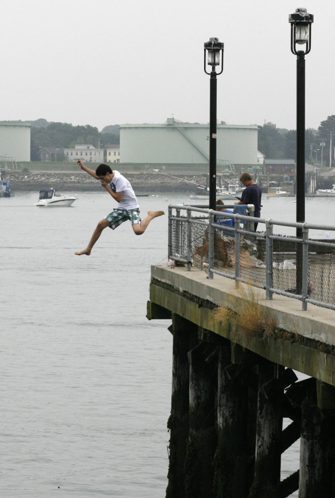 Nathan Delgado leaps from the Maine State Pier into Portland Harbor on Thursday. The city has experienced a string of above-normal temperatures going back to last November and includes the warmest March and April on record.