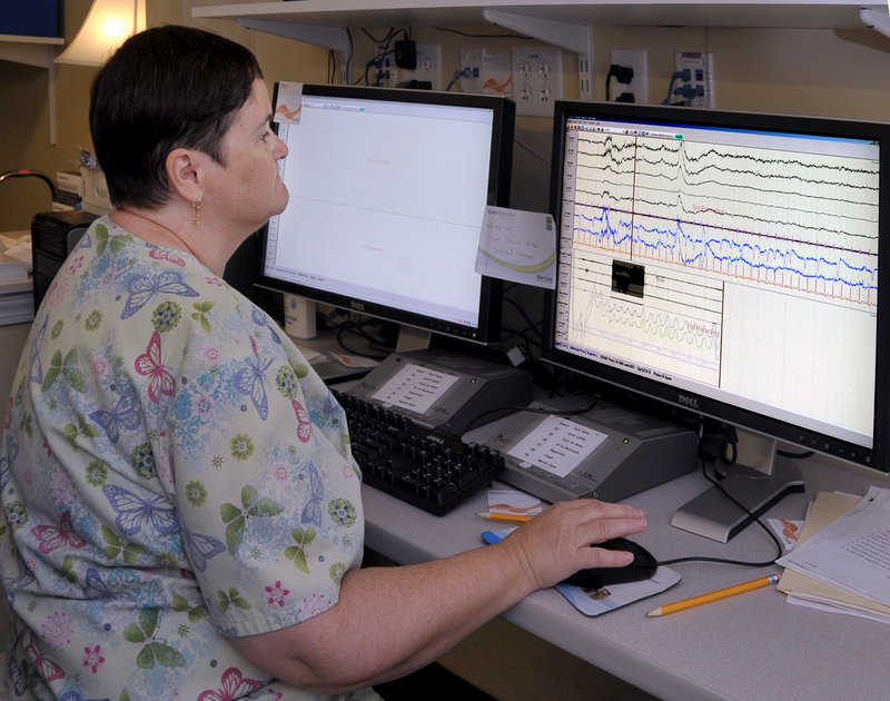 Medical Technician Betsy Eide sets up a computer monitoring program Thursday for one of two patients she will observe overnight for a sleep study at the Comfort Inn.