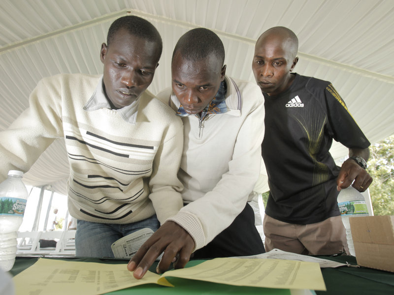 Joel Kemboi Kimurer, left, Stephen Kipkosgei-Kibet and Ed Muge check the list of runners for today's race. Muge will attempt to win the race for the third time.