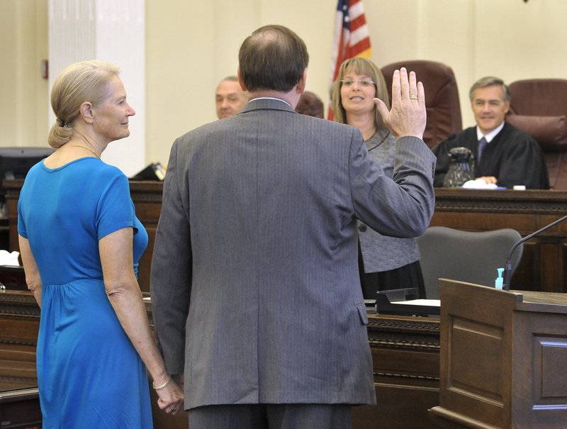 """Thomas Delahanty II, with his wife, Ruth, at his side, is formally sworn in as the new U.S. attorney for Maine at U.S. District Court in Portland on Friday. """"I greatly appreciate the honor of President Obama's nomination,"""" Delahanty told the crowd of legal dignitaries and family members."""