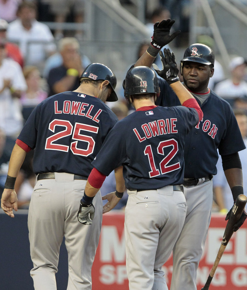 David Ortiz, right, is greeted by Mike Lowell and Jed Lowrie after scoring on Marco Scutaro's two-run double in the second inning.