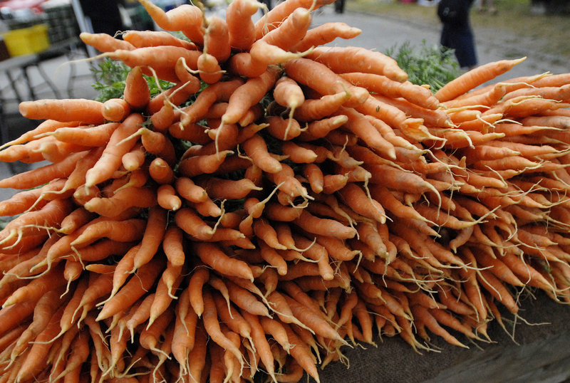 Carrots from South Paw Farm in Unity are arranged in a big, colorful display at the farmers market in Deering Oaks last weekend.
