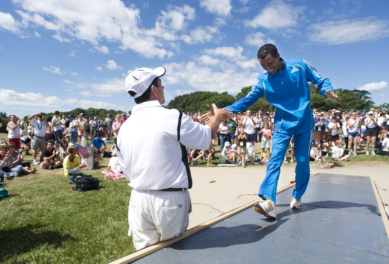 Gebre Gebremariam of Ethiopia climbs the ramp to the awards stage Saturday and receives a hand from Dave McGillivray, the race director, after becoming the first non-Kenyan Beach to Beacon winner since 1999. Gebremariam won $10,000.