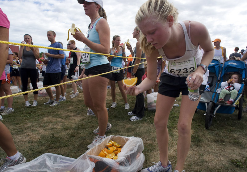 Natalie Rand, 14, of Cape Elizabeth grabs some refreshments after finishing the race. Rand completed the course in 52 minutes, 46 seconds.
