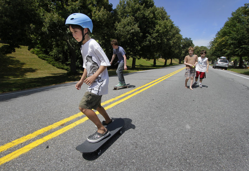 Nine-year-old Henry Spritz skateboards with friends on a section of Baxter Boulevard that was closed down Sunday for the Back Cove Neighborhood Association block party.