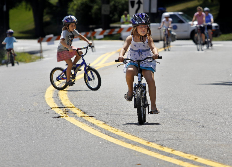 Anya Criden-Clark and her sister Eva, both 7, ride on Baxter Boulevard during Sunday's Back Cove Block Party. The third annual event drew families eager to sample free refreshments, try out hula hoops and use skateboards and inline skates as well as going biking.