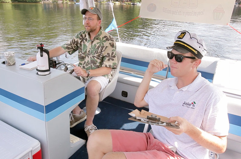 Reporter Ray Routhier pilots a pontoon boat under the guidance of its captain, Jake Viola, on Little Sebago Lake.