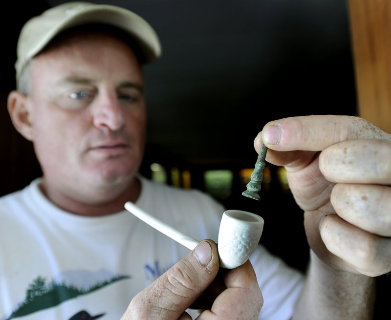 Tom Desjardins, a historian with the Maine Bureau of Public Lands, holds a brass tamper, used to tamp tobacco into a pipe in the late 1600s, that was found during excavations at the historic site this week.