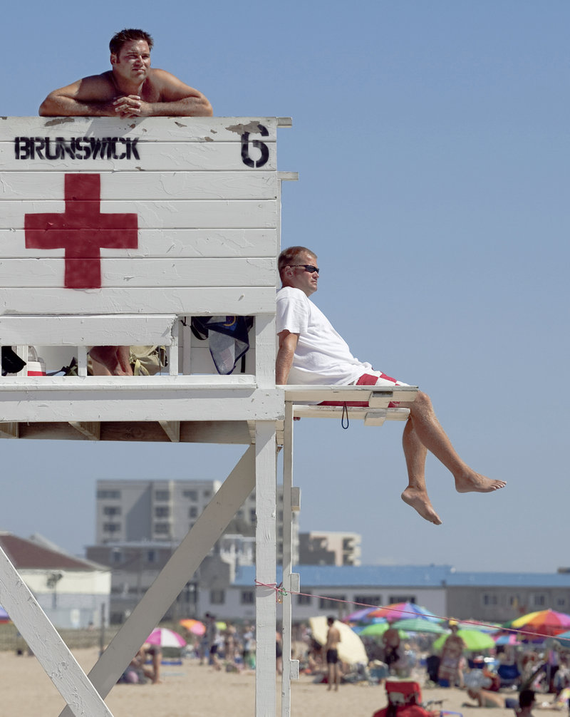 Chief lifeguard Keith Willett, right, and lifeguard Wes Rhames keep an eye on swimmers Wednesday at Old Orchard Beach.