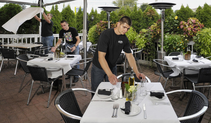 Najib El Karmach, left, Huba Mozes and Atanas Dinkov set the tables on the terrace, one of the dining areas at Angelina's Ristorante and Wine Bar in Ogunquit, in anticipation of a bustling dinner hour.