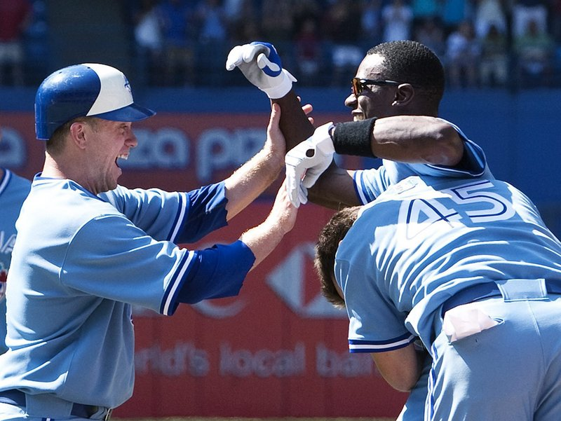 Aaron Hill, left, Fred Lewis, back right, and Travis Snyder celebrate after Hill scored the winning run in Toronto's 6-5 victory over Boston on Thursday. Lewis hit a sacrifice fly after the Blue Jays knocked around Red Sox closer Jonathan Papelbon.