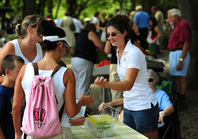 Kate Brun, right, owner of Lucky Leaf Gardens in Harrisburg, N.C., offers a popcorn shoot to a customer at the Harrisburg Farmers Market.