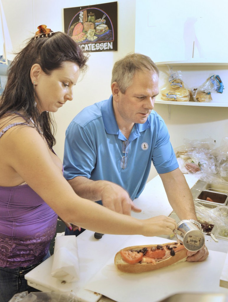 Husband-and-wife team Dan and Minerva Levecque, owners of Ocean House Market on Route 77 in South Portland, prepare sandwiches for customers.