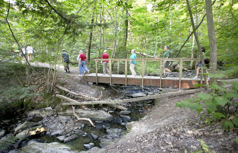 Hikers walk to the Presumpscot River Falls during the Walk Along the Presumpscot Trail Friday. The trail is part of more than 30 miles of trails opened to the public by Portland Trails in the past two decades.