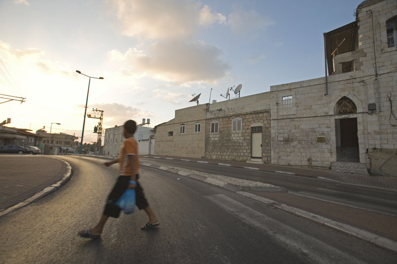 A youth walks by the home of Elias Abuelazam's family in Ramle, Israel. Israeli police said Friday that Abuelazam, a suspect in a string of stabbings in the United States, also was a suspect in a separate stabbing attack in Israel earlier this year, although charges were never pressed.