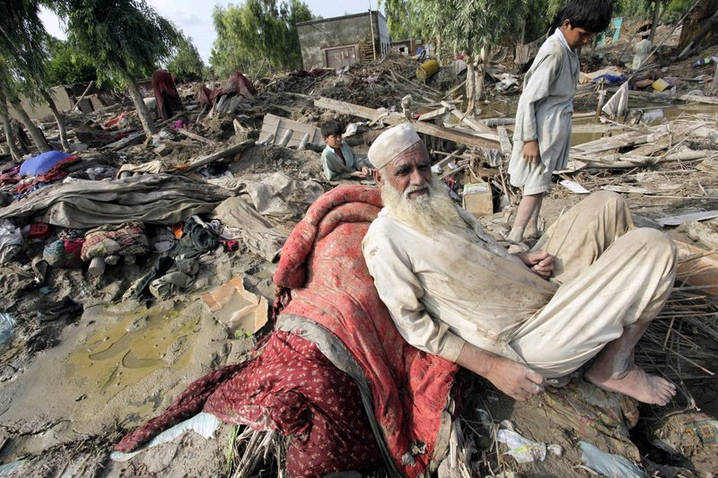 Villagers left homeless by recent floods sit in the rubble of their houses in Aza Khei, Pakistan, on Friday. In terms of the number of people affected, the disaster is worse than the 2004 Indian Ocean tsunami, the 2005 Kashmir earthquake and January's Haiti earthquake combined, the U.N. says.
