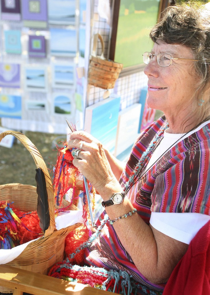 Nancy Clark of Turner knits one of her fancy bags at her booth.
