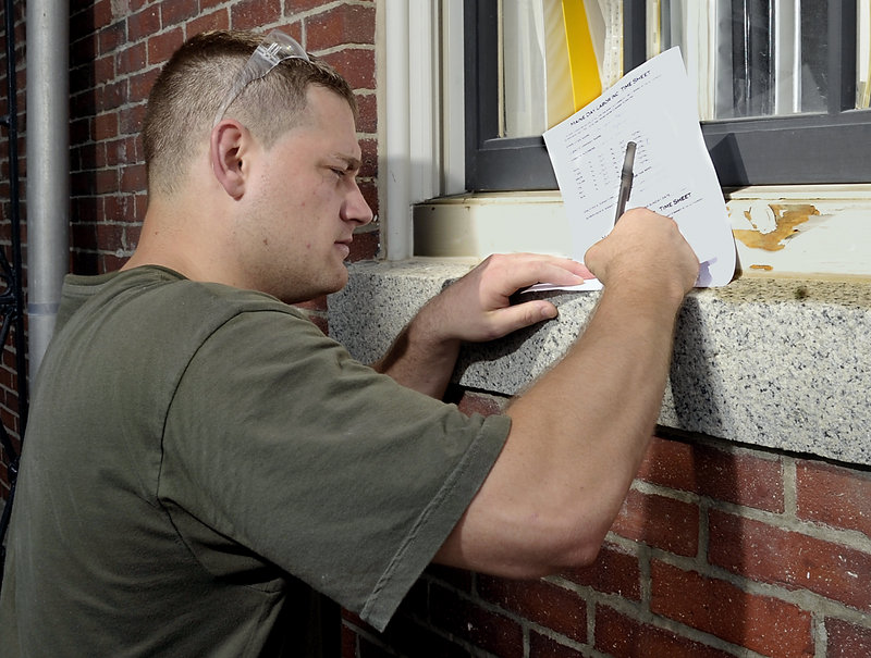 Kyle Crooker, an employee of Maine Day Labor, signs his time sheet before going home for the day. Some of the workers participated in a program at the Maine Correctional Center entailing 60 hours of training in such areas as demonstrating responsibility, problem solving, honesty and interview skills.