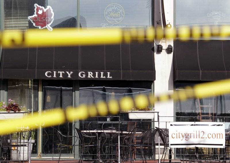 Crime scene tape is stretched across windows that were broken in a train terminal across the street from the City Grill in Buffalo, N.Y., during Saturday's fatal shootings.