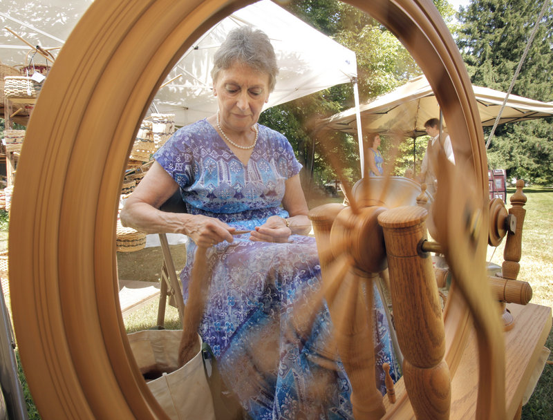Seen through her spinning wheel, Lorrie Hoeh spins alpaca fiber at the Summer Heritage Festival in Bethel on Saturday.