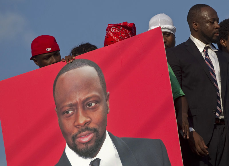 """A supporter holds a portrait of Haitian-born singer Wyclef Jean, a candidate for president. Haiti's """"future is dual citizenship,"""" he says."""