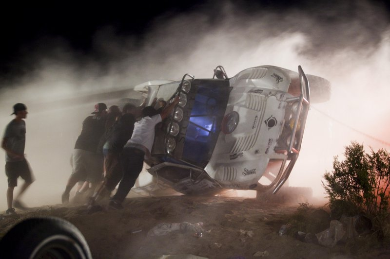 Workers push an overturned off-road truck upright Sunday, after the driver took a jump at high speed and ran into a crowd of spectators at a Lucerne Valley, Calif., race Saturday.