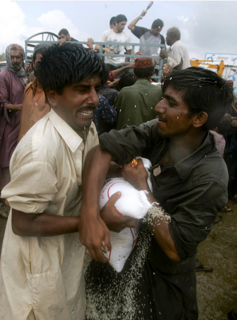 Flood victims grapple for food Monday in Shekarpur, Pakistan. About 20 million people have been affected by the nation's worst disaster.
