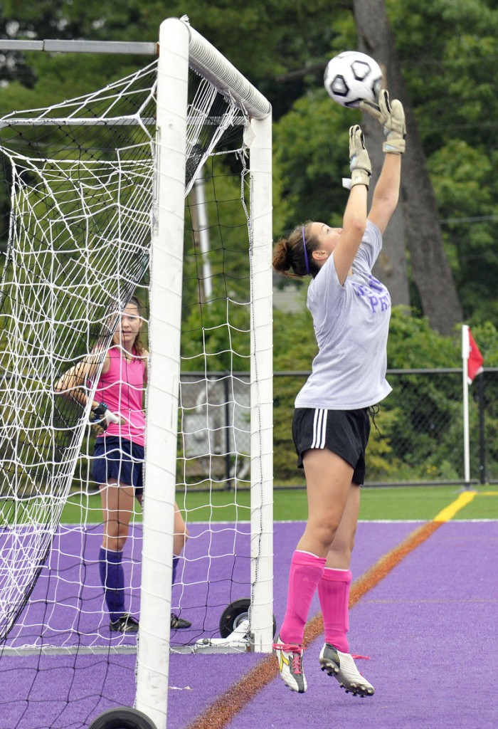 Moira Trynor, a senior goalkeeper, deflects a shot over the crossbar during the Deering girls' soccer team's first practice of the season.
