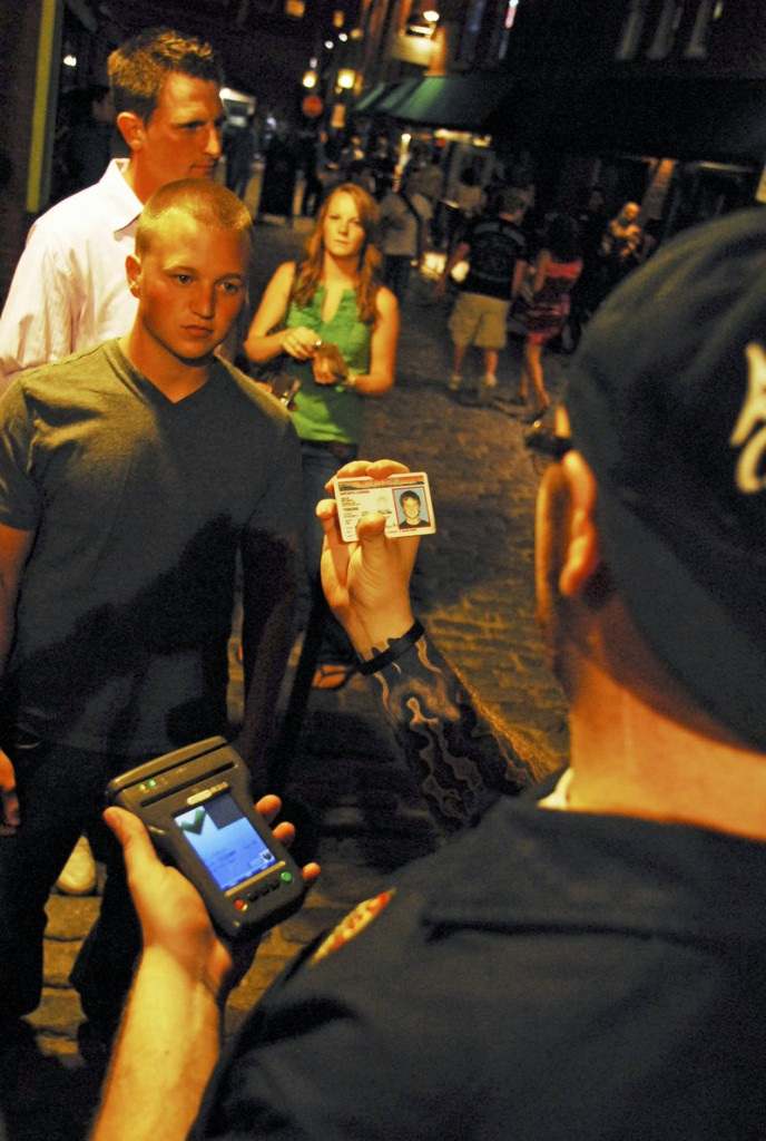Oasis doorman Zack Swander, right, checks IDs at about 11 p.m. on the night of Friday, Aug. 13. Oasis and 51 Wharf are using ID scanners that flag any patrons who have previously caused problems at the bars.
