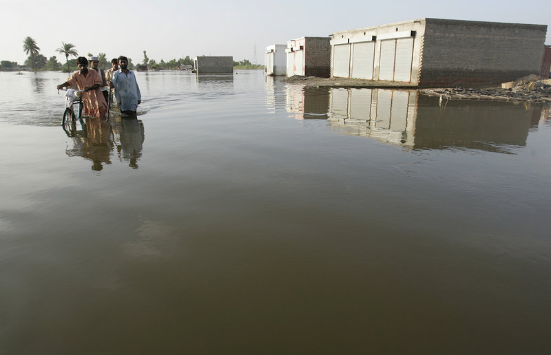 Flood survivors walk through high water near Multan, Pakistan, on Tuesday. The World Bank said it will redirect $900 million of its existing loans to Pakistan to help in flood recovery, as the U.N. warned that many of the millions affected by the disaster have yet to get any aid.