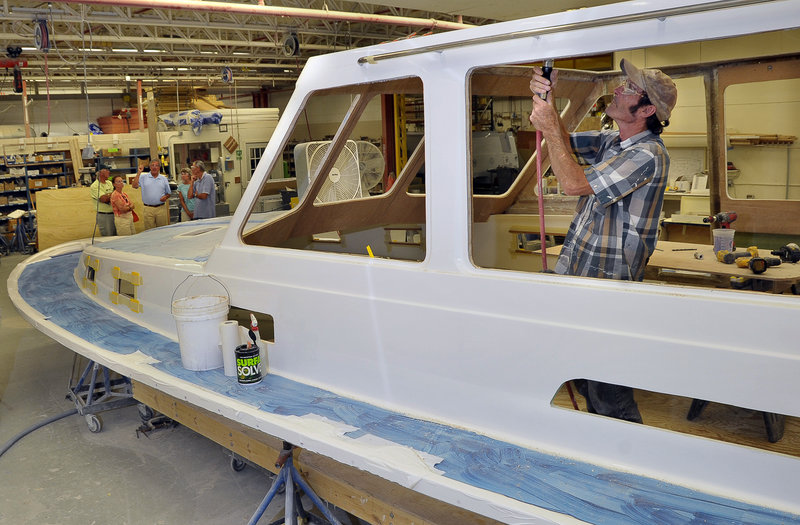 A tour group gets a close-up view of the boat-building process during an open house Tuesday at Sabre Yachts in Raymond.