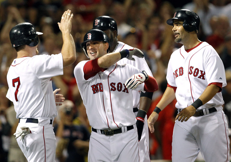 Ryan Kalish, center, celebrates his grand slam with J.D. Drew, left, David Ortiz and Mike Lowell, right, during the fourth inning Tuesday night at Fenway Park.