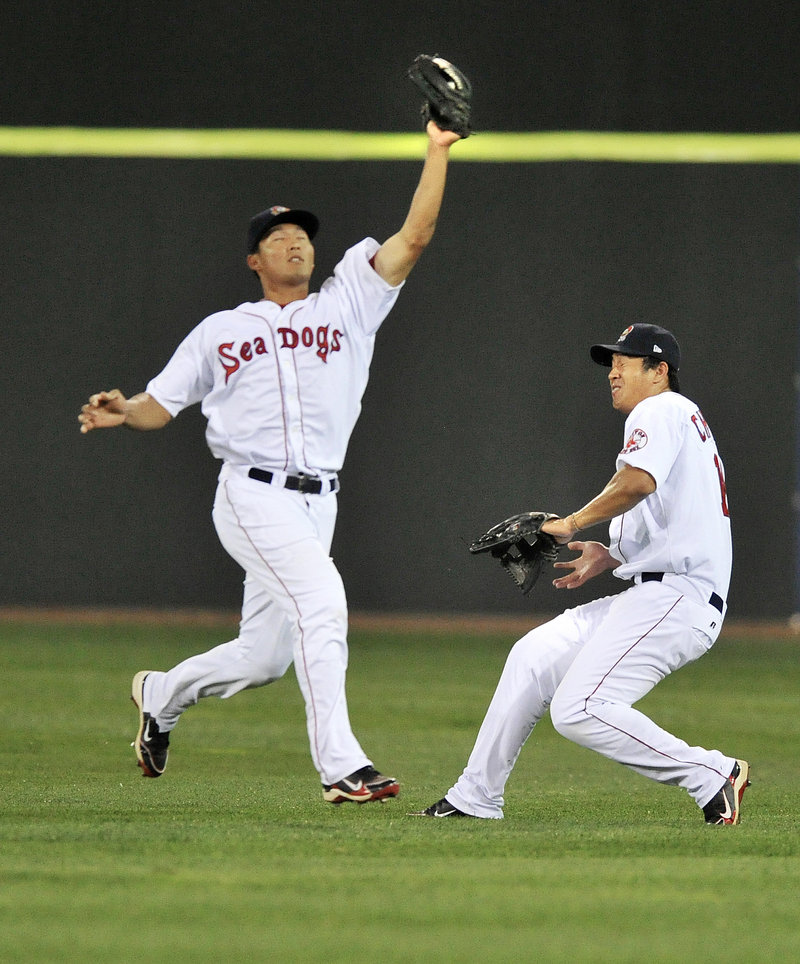 Center fielder Che-Hsuan Lin of the Portland Sea Dogs takes command Tuesday night and pulls in a fly ball in front of right fielder Chih-Hsien Chiang in the fourth inning of a 4-2 loss to the Altoona Curve.