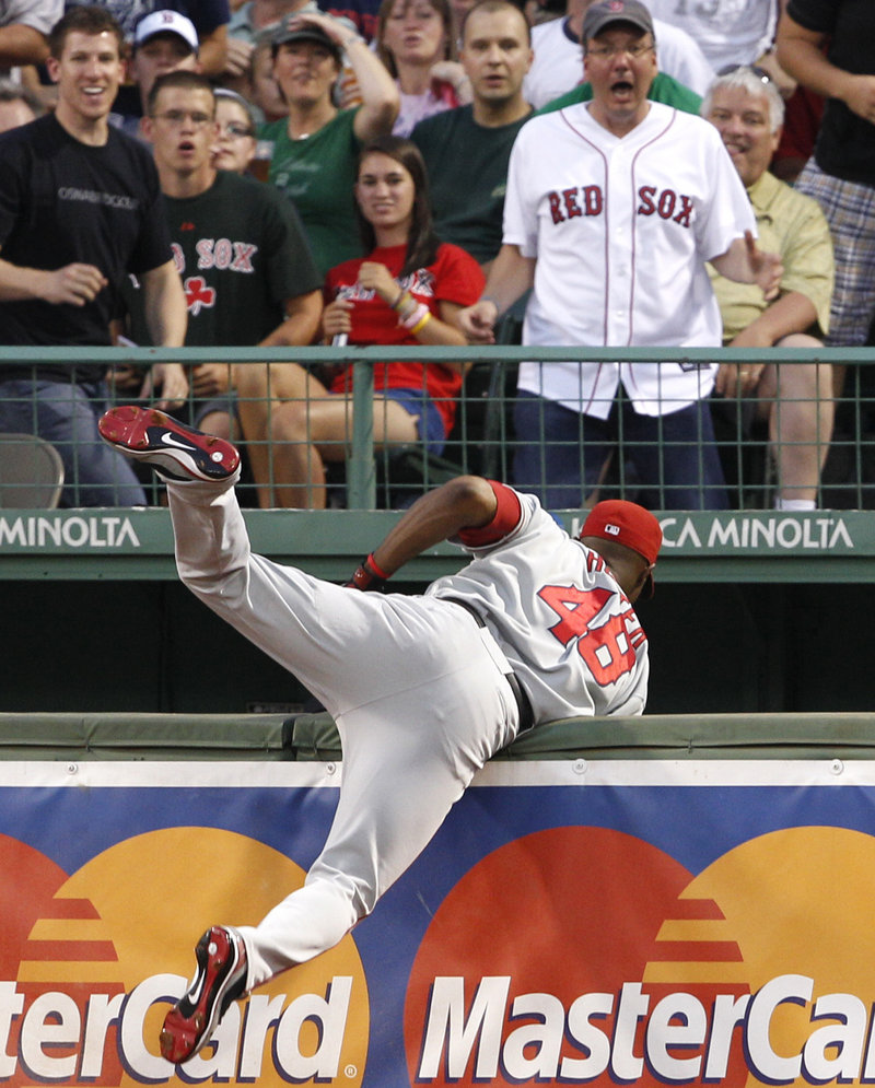 Angels right fielder Torii Hunter almost falls into the bullpen after catching a drive by Boston's Adrian Beltre on Tuesday night at Fenway Park.