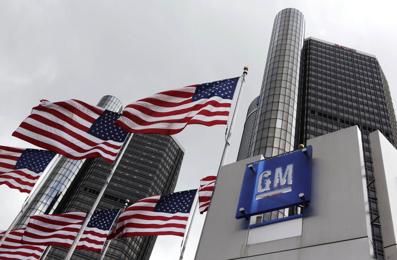 U.S. flags fly at General Motors headquarters in Detroit. GM, 61 percent owned by the federal government, didn't disclose the number of shares that will be sold or the price.
