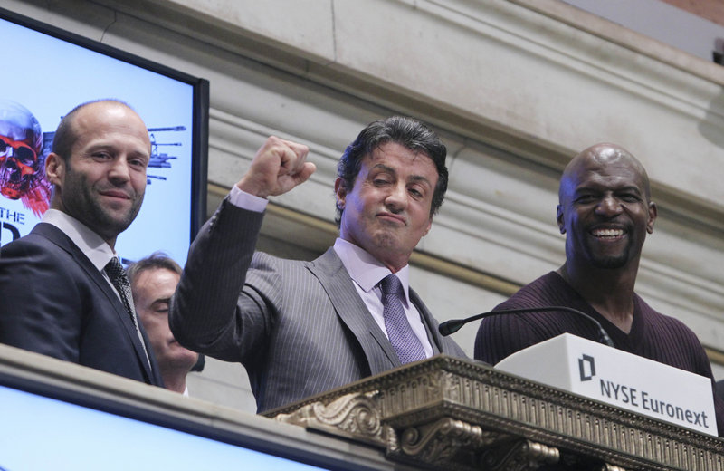 """Cast members from the movie """"The Expendables"""" – from left, Jason Statham, Sylvester Stallone and Terry Crews – ring the opening bell Thursday at the New York Stock Exchange in New York City. As the """"expendables"""" in the action thriller that came out last week, they won more than their share of supercharged street brawls. Wall Street, however, could not be tamed. The Dow Jones industrial average fell 144 points."""