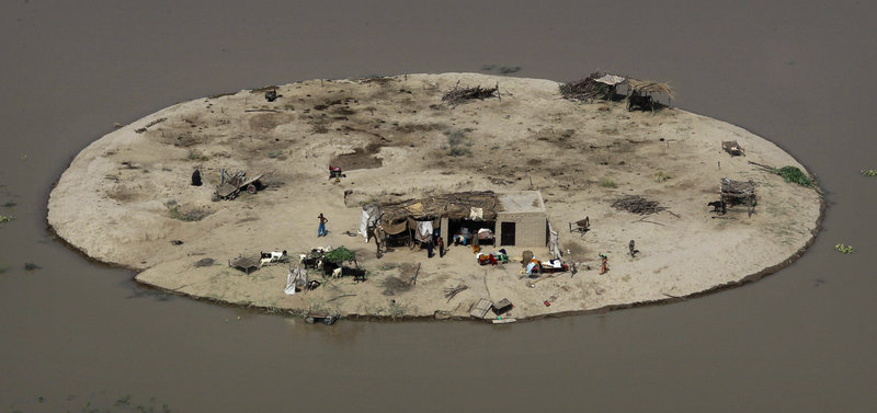 A family is stranded on its farm by floodwaters Thursday near Bachel in Sindh Province, Pakistan. Amid criticism that the international community hasn't done enough to assist flood victims, the United States, Germany and Saudi Arabia announced new pledges of aid.