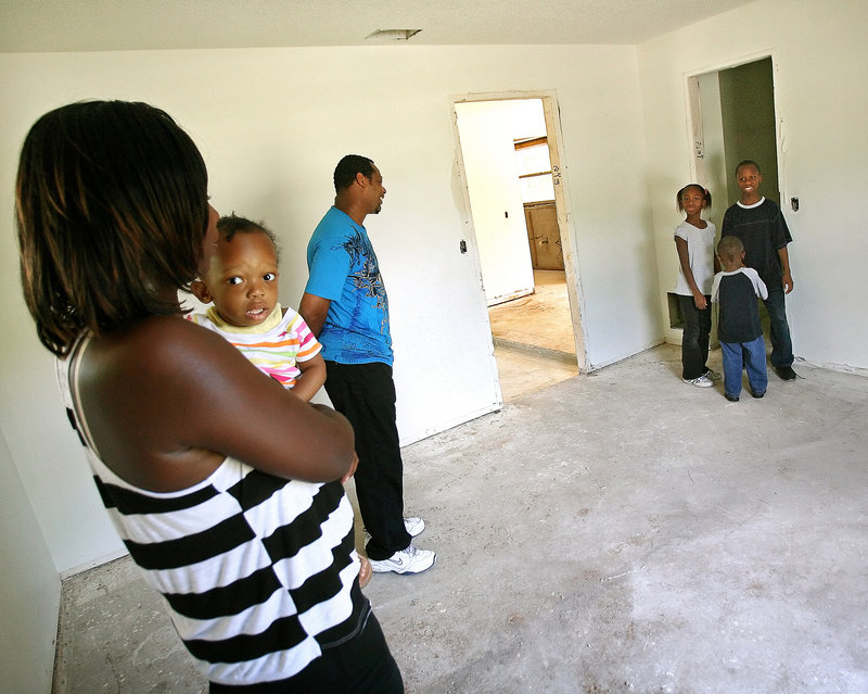 Bruce and Gizzel Stephens tour their future home with four of their children, Shyann, 1, Natalia, 8, Darnell, 3, and Malik, 12. Habitat for Humanity is remodeling a foreclosed home for the family of seven. For Habitat, the rehabbed foreclosures are less expensive than new construction.