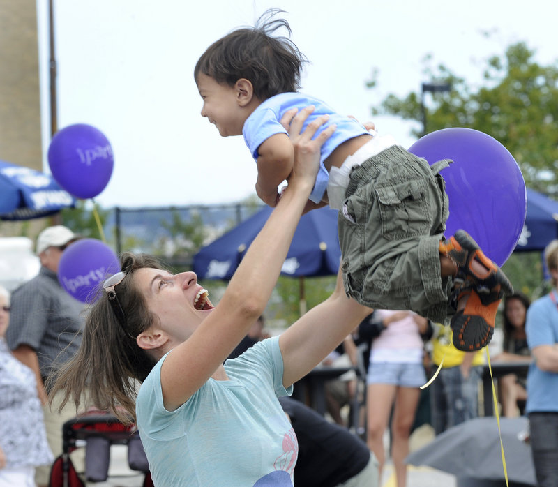 Monica Jalil and her son Remi, 2, of Washington, D.C., dance at the Portland Music and Arts Festival on Saturday.