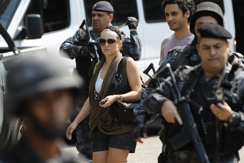 Police stand guard as tourists leave the Intercontinental Hotel in Rio de Janeiro after it was invaded by gunmen Saturday.