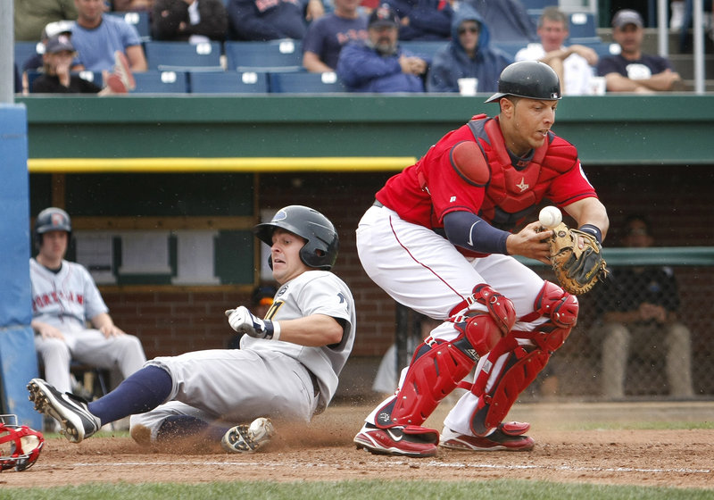 Trenton's Matt Cusick scores on a squeeze bunt as Portland catcher Luis Exposito loses his grip on the ball in the seventh inning Sunday afternoon at Hadlock Field. The Sea Dogs beat the Thunder 7-6 in 11 innings, closing their six-game homestand with a 2-4 record.