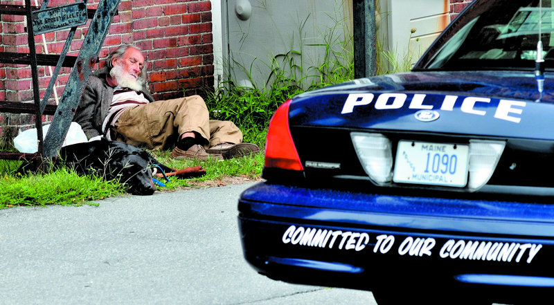 "Rod Rodriquez rests with his dog behind the Skowhegan Police Department on Monday. Rodriquez was taking a break from walking at the ""Nature Park, Nature Trails for the Homeless People of Somerset County,"" a site located in a residential neighborhood in town."