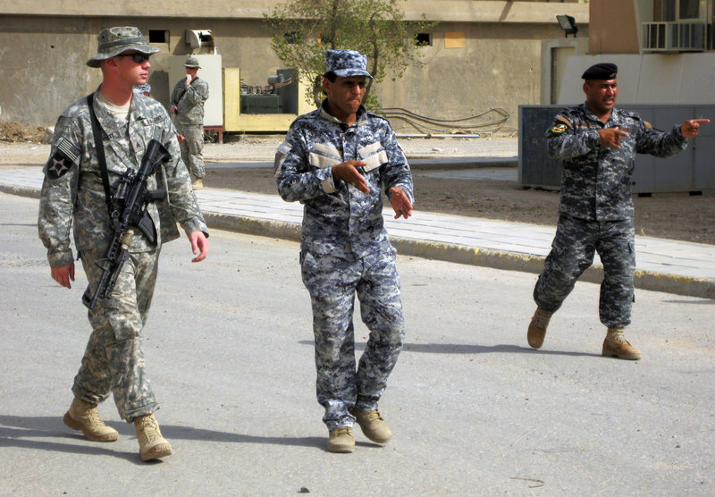"""U.S. Army Sgt. Billy Bennett shows Iraqi police officers how to walk in a """"wedge"""" formation during an exercise. The number of U.S. soldiers in Iraq dipped below 50,000 on Tuesday, a week ahead of a deadline, fulfilling a campaign pledge by President Obama to shift from fighting to a new training mission."""