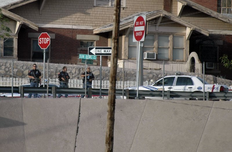 El Paso, Texas, police officers look out into the border city of Ciudad Juarez, Mexico, after a gunbattle erupted in Ciudad Juarez Saturday. A stray bullet from the gunfight crossed the Rio Grande and lodged in a door frame at a university building.