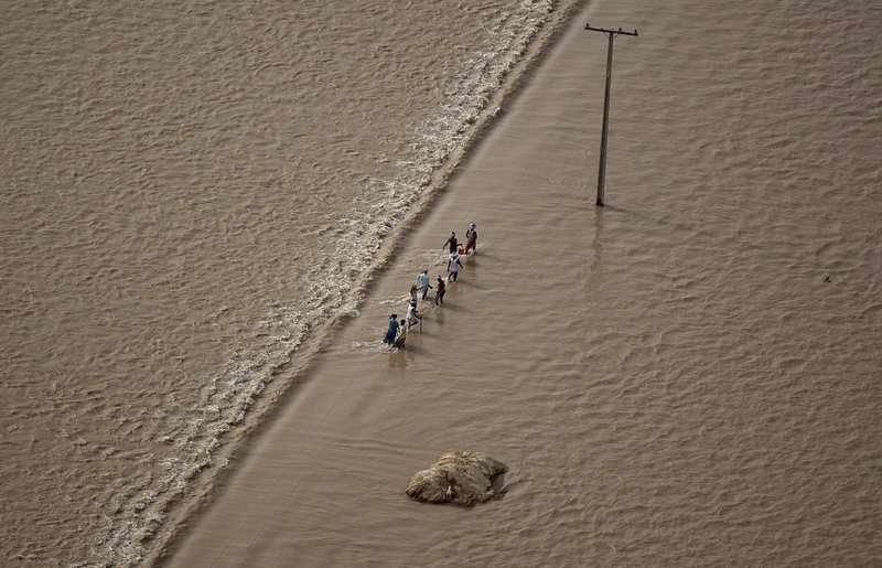 Pakistanis wade through floodwaters Tuesday near Thul, a town in Sindh province. The U.N. High Commissioner for Refugees estimates that about 700,000 Pakistanis have been forced into makeshift settlements just in the southern province of Sindh.