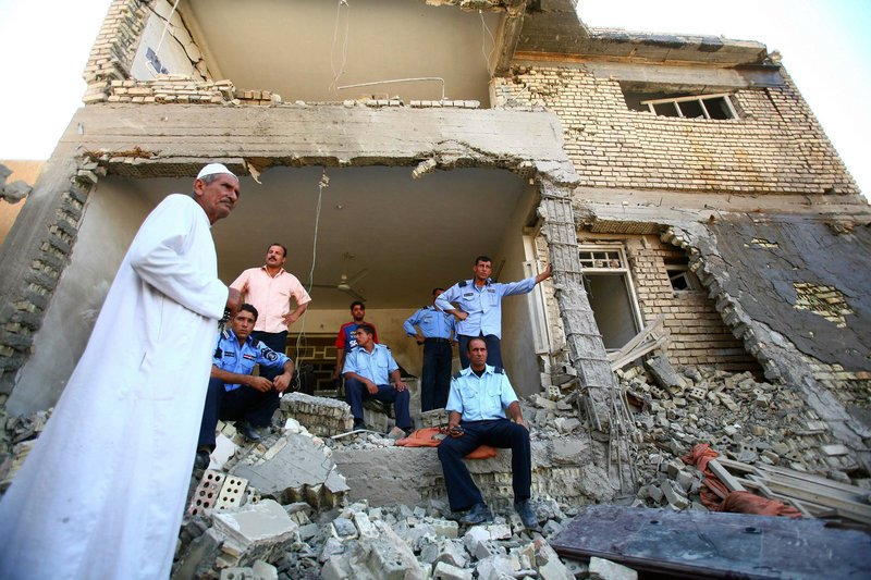 Iraqi bystanders and police officers congregate in the rubble of a building Wednesday in Karbala. Iraqi security officials blamed the Sunni extremist group al-Qaida in Iraq for coordinated bombings in a dozen cities and towns across the country.