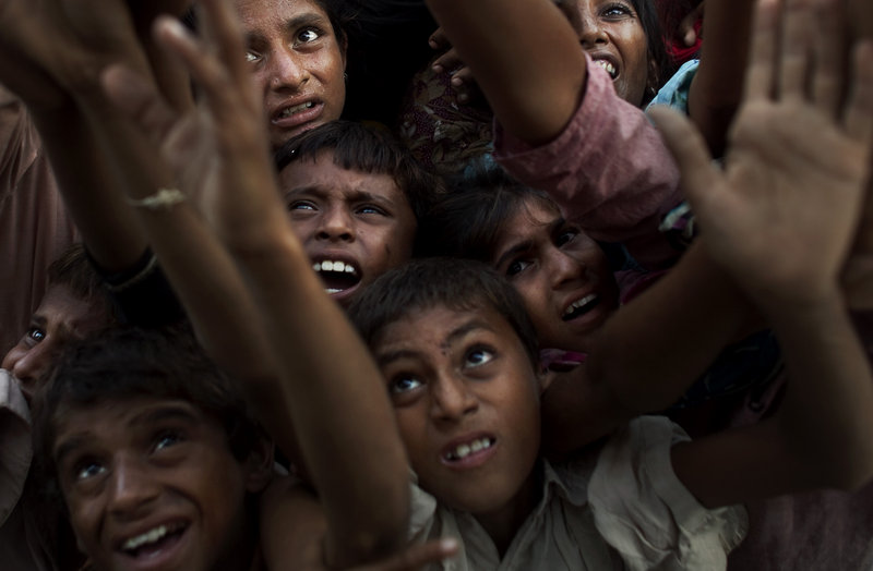 Children displaced by floods vie for milk Wednesday at a temporary camp in Sukkar, Sindh province, southern Pakistan. The floods, triggered by the start of monsoon rains a month ago, have submerged one-fifth of the nation, washed away entire settlements and sparked fears of unrest.